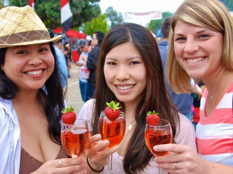 Friends enjoying a strawberry-flavored cocktail at the California Strawberry Festival in Oxnard